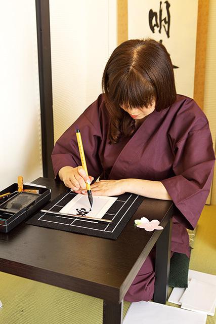 漢字名付け体験のプロセス4「書道人の書道」 漢字が決定したら、すぐさま 書道人(書道が得意な人)が 漢字をしたため、額縁に収める。 待つ間、折り紙なども教えてくれる。