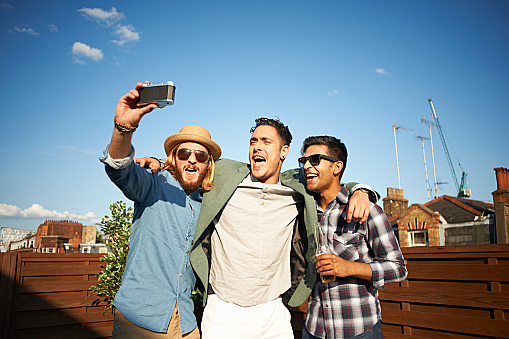 Three male friends taking camera selfie at rooftop party