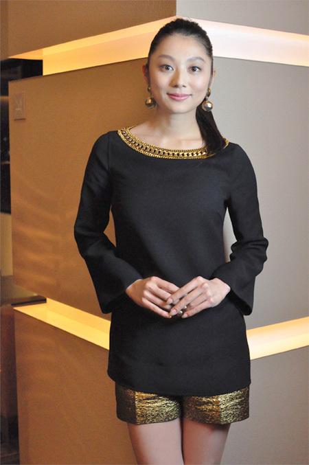 黒の服に金色のアクセントのある服を着る小池栄子