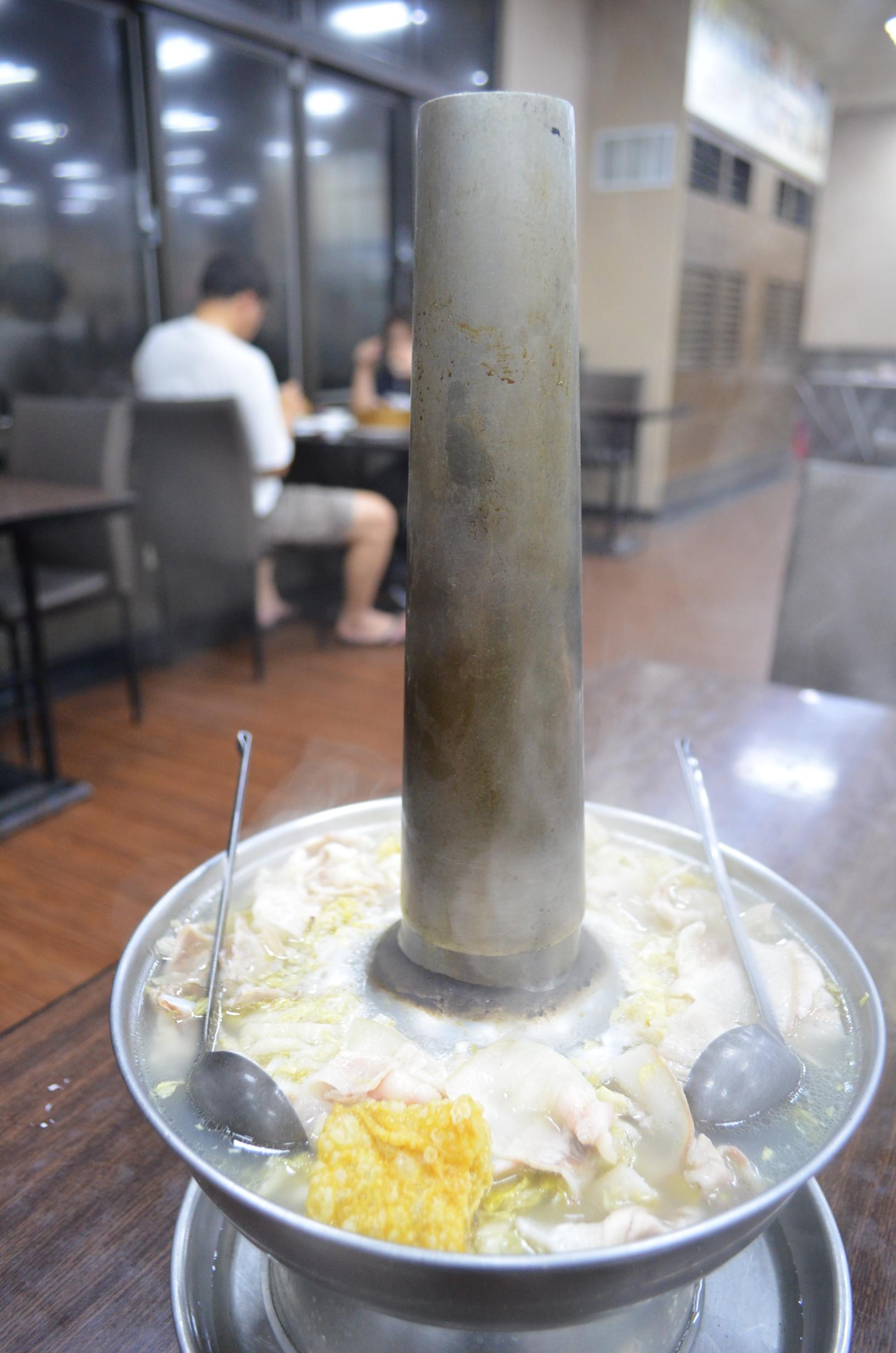 見上げるような煙突が付きだした鍋にたっぷりの酸白菜と豚肉が入る