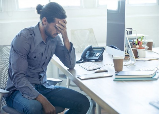 Stressed business man at the office. He is casually dressed and looking distraught. He looks very uncomfortable and could also have a headache. He is has his head in his hand and looks very upset. Hi is sitting at a desk with a computer and phone. Copy space.